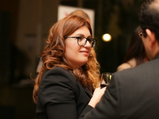 Lady with long brown hair holding glass of wine talking to a man at a business event