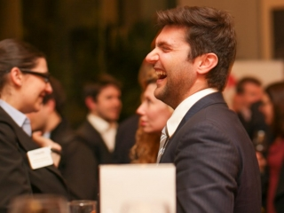 Man laughing in navy suit at corporate event