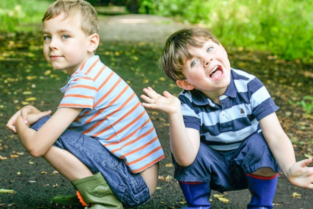 young brothers in wellington boots crouching down in the garden