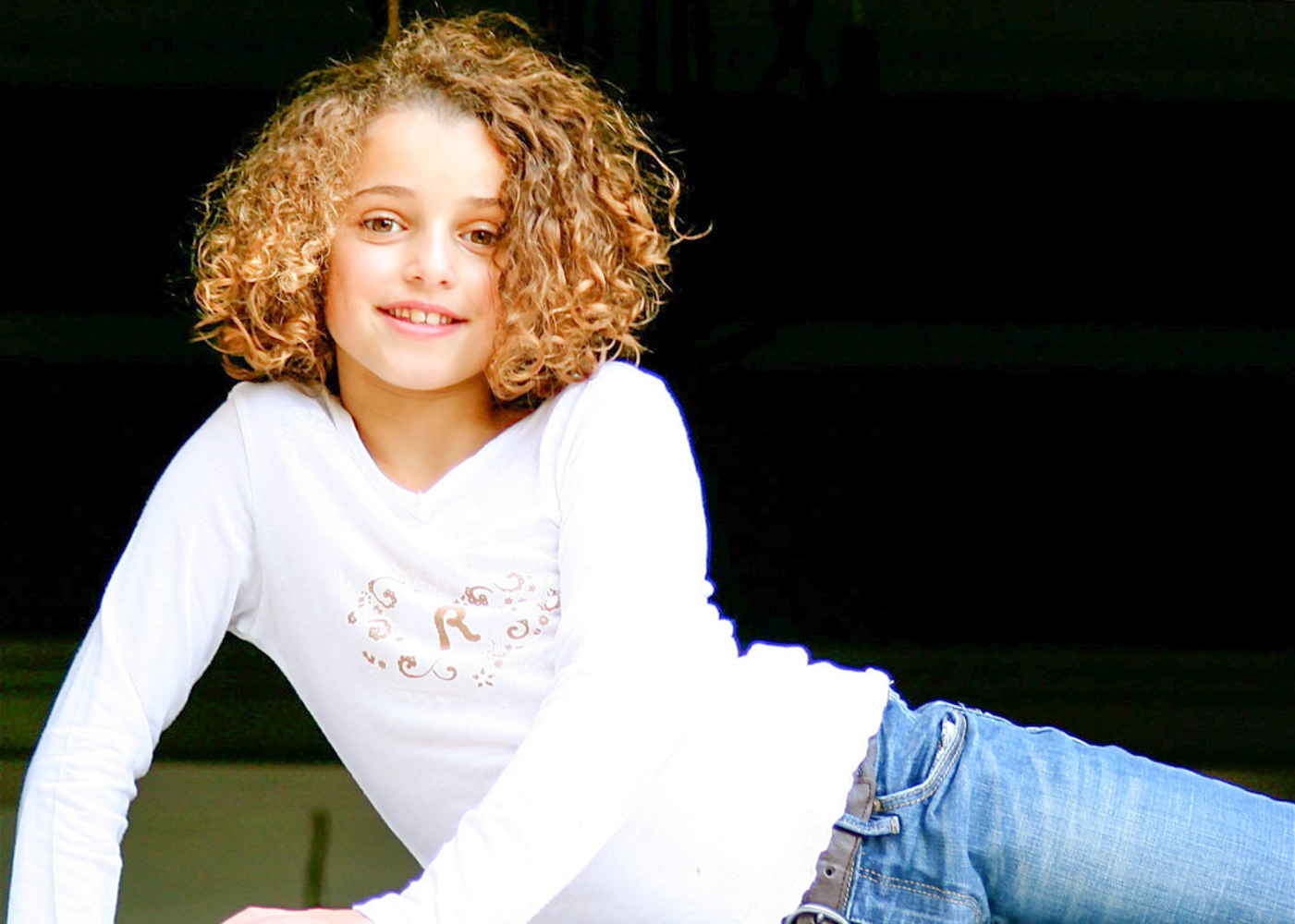 teenage girl with curly brown hair in white long-sleeved t-shirt