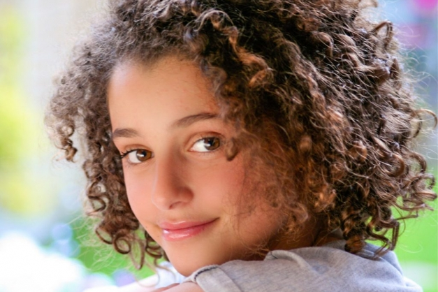 Teenage girl with curly brown hair smiling at camera