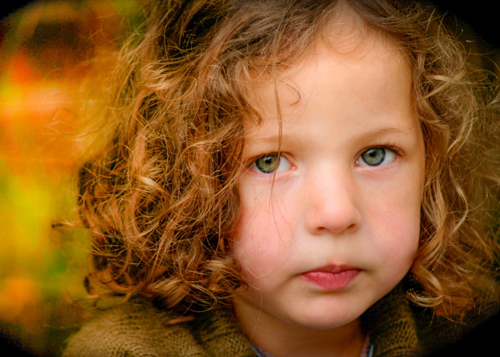 close up of young girl with green eyes and curly blond hair