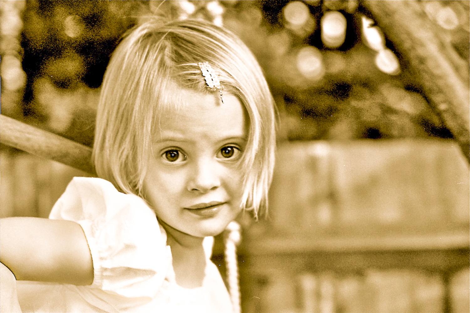 sepia image of young girl with short blond hair with a clip in her hair looking at camera