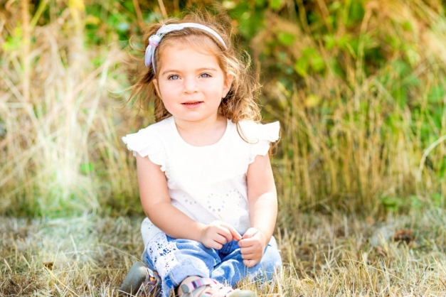 Young child with white top sitting on the grass