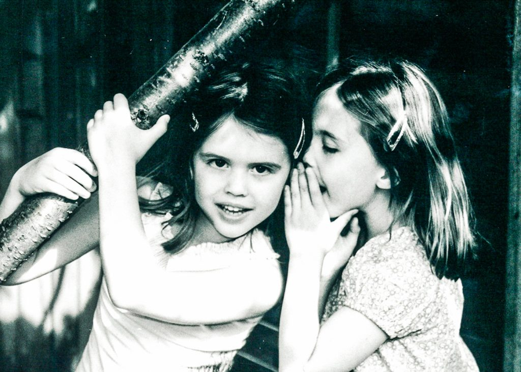 black and white photo of a little girl whispering to her friend outside in a garden