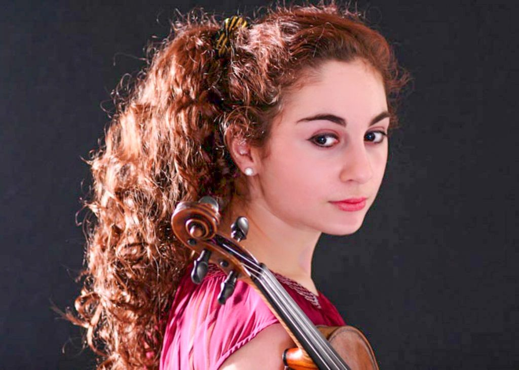 Headshot of young lady with long curly brown hair holding violin