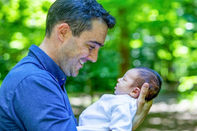 Man in blue shirt gazing at new born baby in the garden