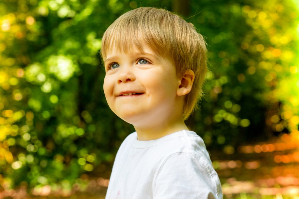 Young boy with blond hair and blue eyes smiling in the garden